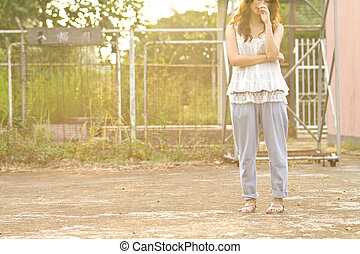 Asian woman standing and thinking in basketball court, half body image, let people have more imagination.