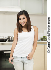 Asian woman standing at home in her kitchen