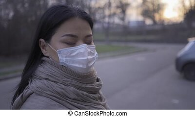 Asian woman standing in pollution mask in empty city during quarntine.