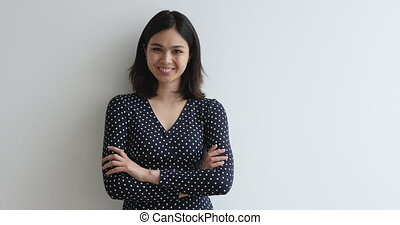 Asian woman standing with arms crossed laughing looking at ...