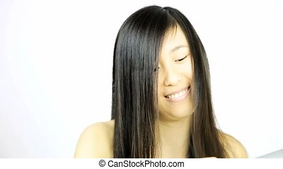 Asian woman straightening hair