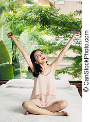 Asian woman stretching sitting on bed in the morning