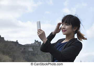 Happy Chinese woman, taking self portrait with her phone Camera Outdoors.