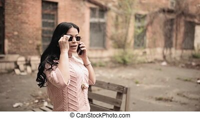 Asian woman answering phone while photo session and talking during working on camera wearing pink outfit and standing on old industrial factory background.