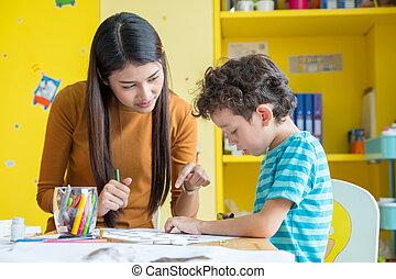 Asian woman teacher teaching boy kid to paint color book on table in classroom,kindergarten education school
