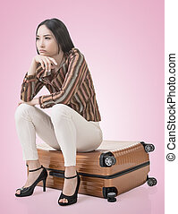 Asian woman thinking and sitting on a luggage