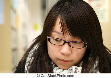 Asian woman thinking and studying in library