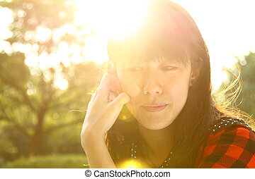 Asian woman thinking under sunshine