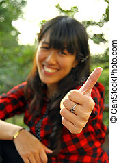 Asian woman thumbs up outdoor