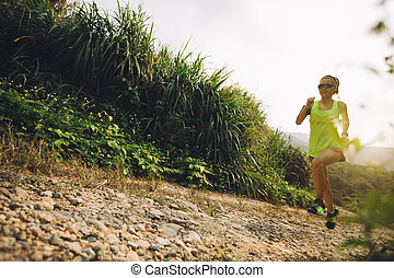 Asian woman trail running on mountain