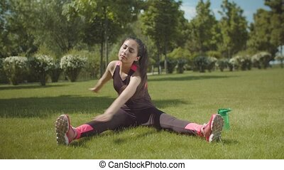 Asian woman training muscles sitting on park lawn - Chinese...