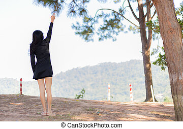 Asian woman trying to touch the branch of pine.