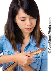 Asian woman tunning ukelele
