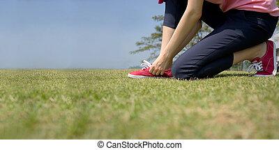 asian woman tying shoelace