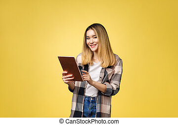 Asian woman use of tablet pc isolate on yello background.