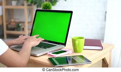 Asian woman Using A Green Screen Notebook Computer