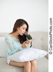 Asian woman using smartphone sitting on couch