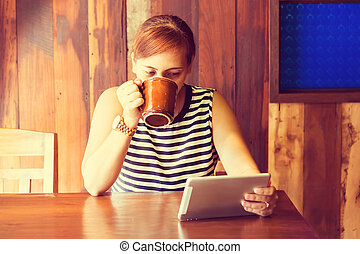 Asian woman using tablet computer in cafe drinking coffee. Focus on her face and mug. (Vintage process tone)