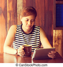 Asian woman using tablet computer in cafe drinking coffee. Focus on her face. (Vintage process tone)