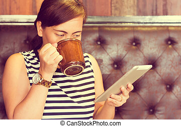 Asian woman using tablet computer in cafe drinking coffee. Focus on mug. (Vintage process tone)