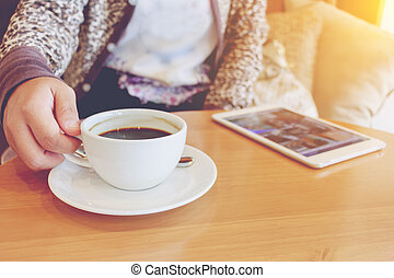 Asian woman using tablet computer in cafe drinking coffee.