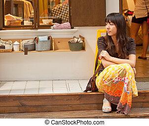 Asian woman waiting alone