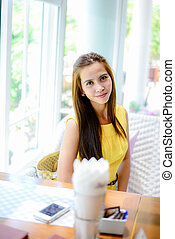 Asian woman waiting for food in restaurant
