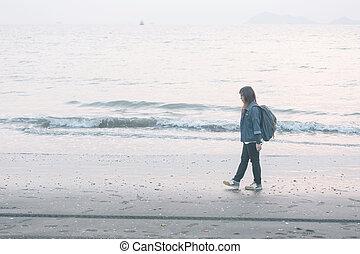 Asian woman walking along beach