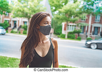 Asian woman walking in city street wearing face mask for COVID 19 prevention. Happy young student with fashion pattern cloth mouth covering outside. Corona virus concept