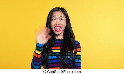 Asian woman waving hello or goodbye to camera and slowly ...