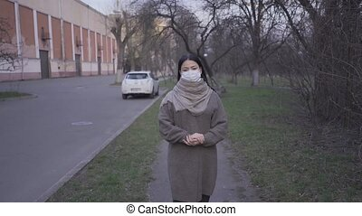 Asian woman wearing pollution mask standing outdoors.