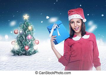 Asian woman wearing santa hat holding present