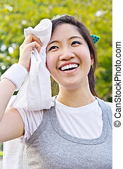 Asian woman wiping sweat with towel