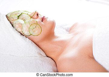 facial mask and cucumber - asian woman with a facial mask...