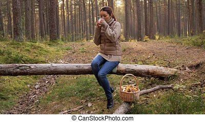 asian woman with mushrooms drinking tea in forest - picking ...