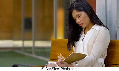 asian woman with notebook or sketchbook on bench - leisure,...