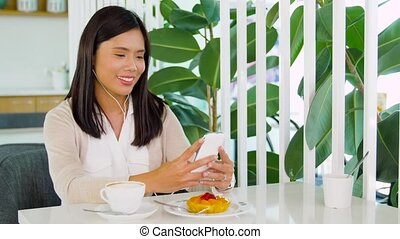 asian woman with smartphone and earphones at cafe -...