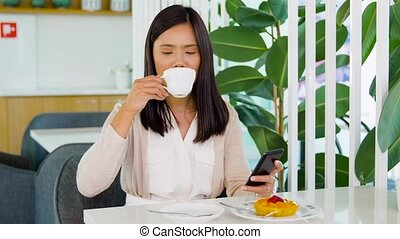 asian woman with smartphone at cafe or coffee shop -...