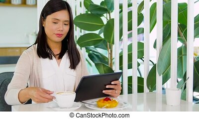 asian woman with tablet pc at cafe or coffee shop -...