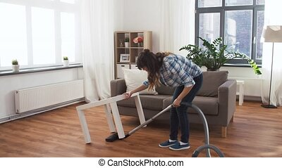 asian woman with vacuum cleaner at home