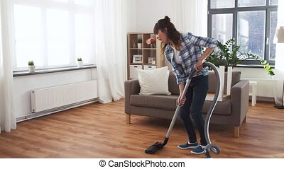 asian woman with vacuum cleaner having fun at home -...