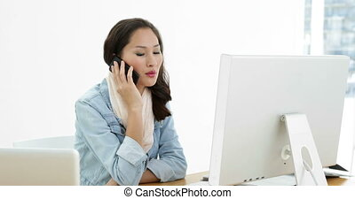Asian woman working at desk using computer talking on the...