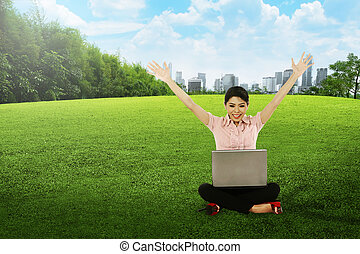 Asian woman working with laptop and sitting on the grass