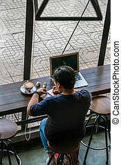 Asian woman writing notes in the cafe