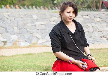 Asian women black shirt. Sitting on the lawn.