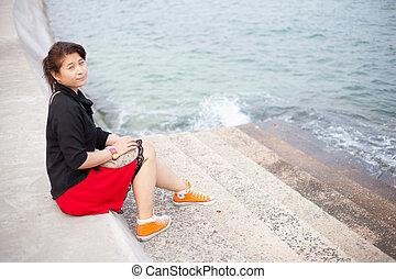 Asian women black shirt. Sitting on the pavement.