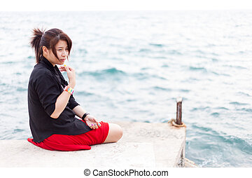 Asian women black shirt. Sitting on the sidewalk.