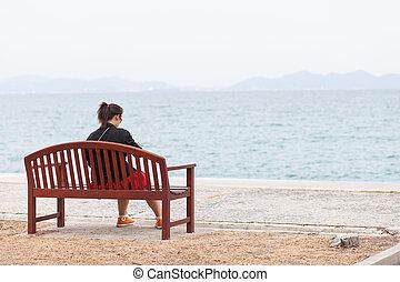 Asian women black shirt. Sitting on wooden bench.