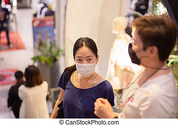Asian women in protective mask standing on escalator in shopping mall.