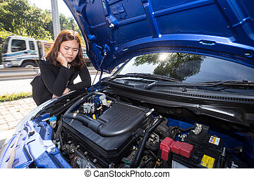 Asian women opened the hood and looking at broken down car engine on street